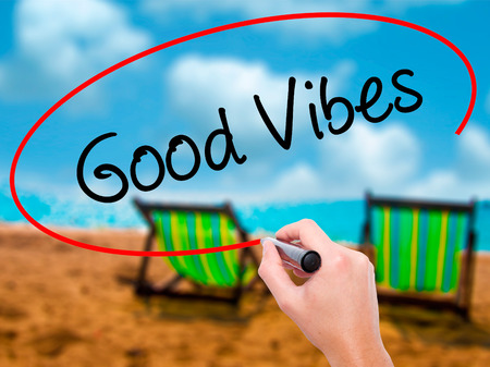 positivismo: Man Hand writing Good Vibes with black marker on visual screen. Isolated on sunbed on the beach. Business, technology, internet concept. Stock Photo