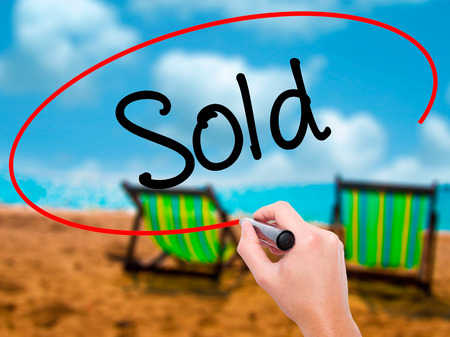 Man Hand writing Sold with black marker on visual screen. Isolated on sunbed on the beach. Business, technology, internet concept. Stock Photo