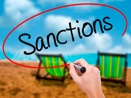 sanctioned: Man Hand writing Sanctions with black marker on visual screen. Isolated on sunbed on the beach. Business, technology, internet concept. Stock  Photo