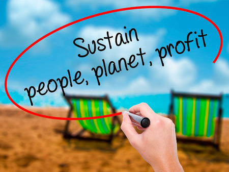 sustain: Man Hand writing Sustain, people, planet, profit with black marker on visual screen. Isolated on sunbed on the beach. Business, technology, internet concept. Stock Photo