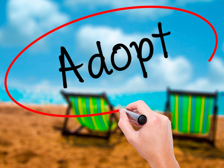 mother in law: Man Hand writing Adopt  with black marker on visual screen. Isolated on sunbed on the beach. Business, technology, internet concept. Stock Photo
