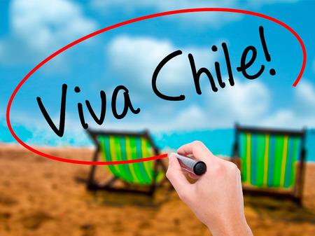 bandera chilena: ¡Mano de hombre escribiendo Viva Chile! con marcador negro en la pantalla visual. Aislado en hamaca en la playa. Negocios, tecnología, concepto de internet. Imagen del editor Foto de archivo