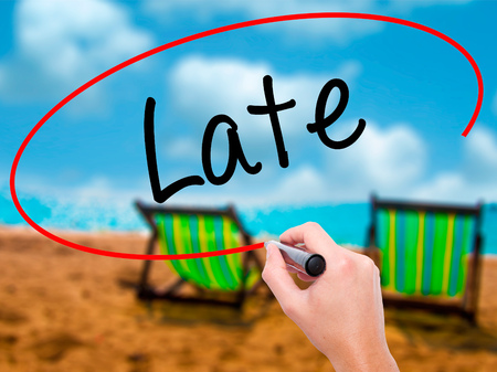 Man Hand writing Late with black marker on visual screen. Isolated on sunbed on the beach. Business, technology, internet concept. Stock Photo Stock Photo