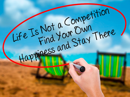 Man Hand writing Life Is Not a Competition Find Your Own Happiness and Stay There  with black marker on visual screen. Isolated on sunbed on the beach. Business, technology, internet concept. Stock Photo Stock Photo