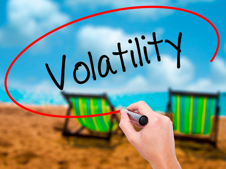 volatility: Man Hand writing Volatility with black marker on visual screen. Isolated on sunbed on the beach. Business, technology, internet concept. Stock Photo Stock Photo