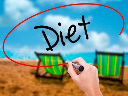 Man Hand writing Diet (in Portuguese)  with black marker on visual screen. Isolated on sunbed on the beach. Business, technology, internet concept. Stock Photo
