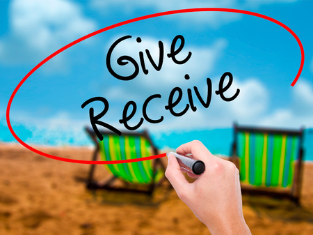 bestowing: Man Hand writing Give Receive with black marker on visual screen. Isolated on sunbed on the beach. Business, technology, internet concept. Stock Photo Stock Photo