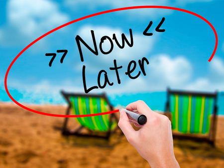 Man Hand writing NowLater with black marker on visual screen. Isolated on sunbed on the beach. Business, technology, internet concept. Stock Photo