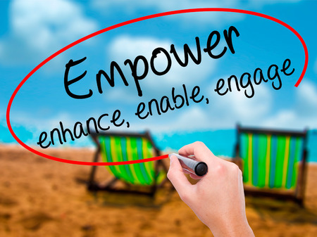 Man Hand writing Empower enhance, enable, engage with black marker on visual screen. Isolated on sunbed on the beach. Business, technology, internet concept. Stock Photo