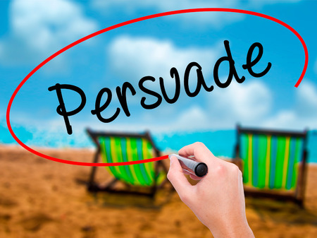 persuade: Man Hand writing Persuade with black marker on visual screen. Isolated on sunbed on the beach. Business, technology, internet concept. Stock Photo