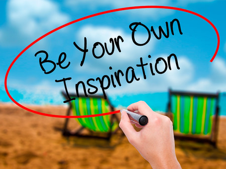owning: Man Hand writing Be Your Own Inspiration with black marker on visual screen. Isolated on sunbed on the beach. Business, technology, internet concept. Stock Photo
