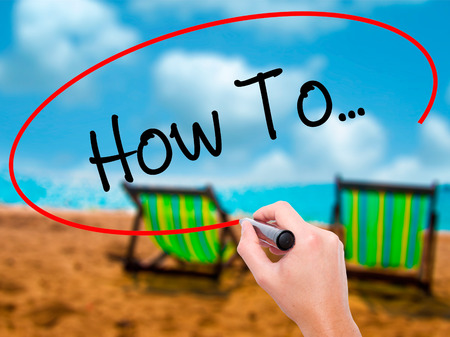 Man Hand writing How To...  with black marker on visual screen. Isolated on sunbed on the beach. Business, technology, internet concept. Stock Photo Stock Photo