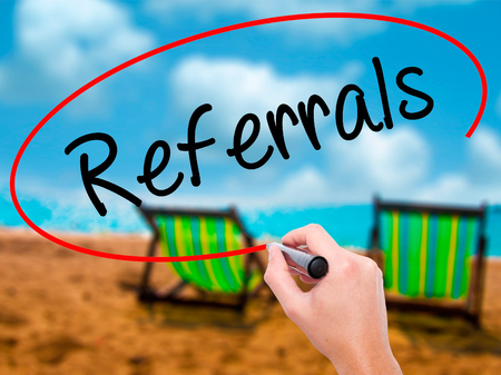 Man Hand writing Referrals with black marker on visual screen. Isolated on sunbed on the beach. Business, technology, internet concept. Stock Photo