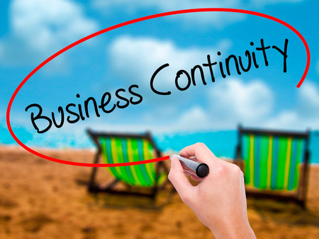Man Hand writing Business Continuity with black marker on visual screen. Isolated on sunbed on the beach. Business, technology, internet concept. Stock Photo Stock Photo