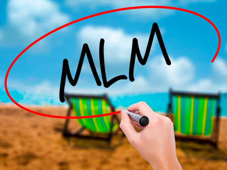 multilevel: Man Hand writing  MLM (Multi-Level Marketing) with black marker on visual screen. Isolated on sunbed on the beach. Business, technology, internet concept. Stock Photo Stock Photo