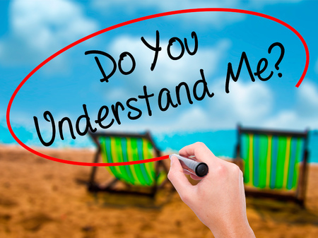 understand: Man Hand writing Do You Understand Me? with black marker on visual screen. Isolated on sunbed on the beach. Business, technology, internet concept. Stock Photo
