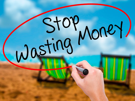 Man Hand writing Stop Wasting Money with black marker on visual screen. Isolated on sunbed on the beach. Business, technology, internet concept. Stock Photo Stock Photo