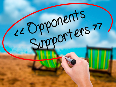 Man Hand writing Opponents - Supporters with black marker on visual screen. Isolated on sunbed on the beach. Business, technology, internet concept. Stock Photo