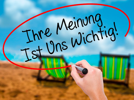 Man Hand writing Ihre Meinung Ist Uns Wichtig! (Your Opinion is Important to Us in German) with marker on visual screen. Isolated on sunbed on the beach. Business, technology, internet concept. Stock Photo