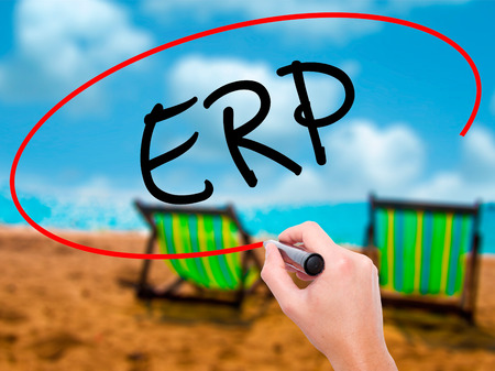 Man Hand writing  ERP (Enterprise Resource Planning)   with black marker on visual screen. Isolated on sunbed on the beach. Business, technology, internet concept. Stock Photo Stock Photo