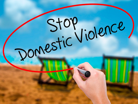 coward: Man Hand writing  Stop Domestic Violence with black marker on visual screen. Isolated on sunbed on the beach. Business, technology, internet concept. Stock Photo Stock Photo