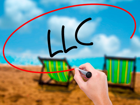 Man Hand writing  LLC (Limited Liability Company)  with black marker on visual screen. Isolated on sunbed on the beach. Business, technology, internet concept. Stock Photo