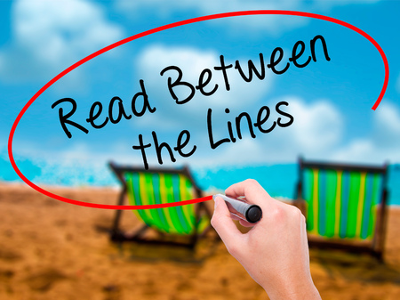 Man Hand writing Read Between the Lines   with black marker on visual screen. Isolated on sunbed on the beach. Business, technology, internet concept. Stock Photo Stock Photo