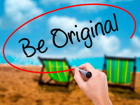Man Hand writing Be Original with black marker on visual screen. Isolated on sunbed on the beach. Business, technology, internet concept. Stock Photo