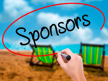 Man Hand writing Sponsors with black marker on visual screen. Isolated on sunbed on the beach. Business, technology, internet concept. Stock Photo