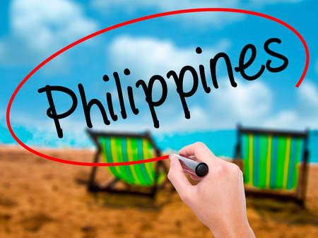 Man Hand writing Philippines with black marker on visual screen. Isolated on sunbed on the beach. Business, technology, internet concept. Stock Photo