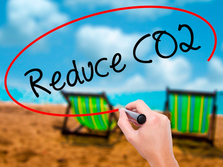 Man Hand writing Reduce CO2 with black marker on visual screen. Isolated on sunbed on the beach. Business, technology, internet concept. Stock Photo