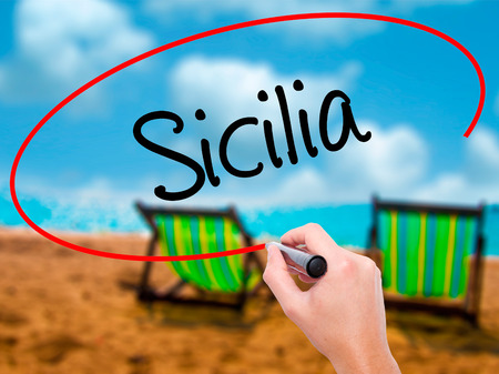 Man Hand writing Sicilia (Sicily In Italian)  with black marker on visual screen. Isolated on sky. Business, technology, internet concept. Stock Photo
