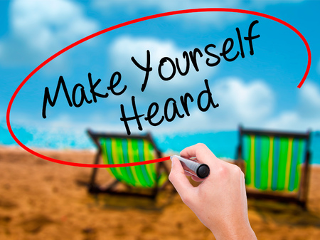 heard: Man Hand writing Make Yourself Heard with black marker on visual screen. Isolated on sunbed on the beach. Business, technology, internet concept. Stock Photo Stock Photo