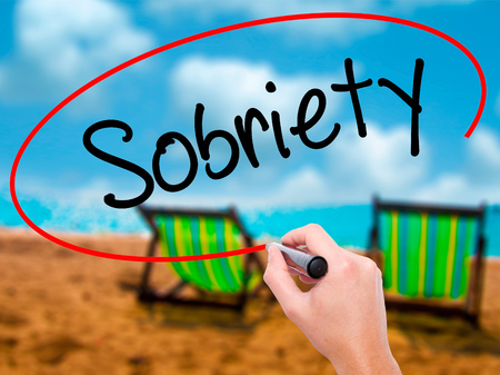 sobriety: Man Hand writing Sobriety with black marker on visual screen. Isolated on sunbed on the beach. Business, technology, internet concept. Stock Photo