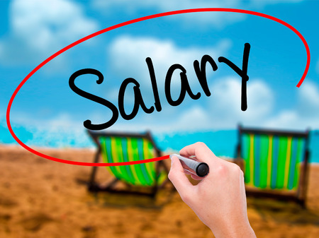 remuneración: Man Hand writing Salary  with black marker on visual screen. Isolated on sunbed on the beach. Business, technology, internet concept. Stock Photo