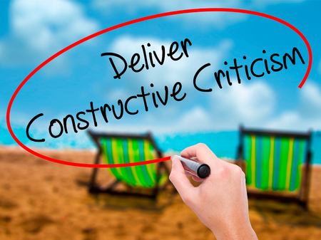 criticism: Man Hand writing Deliver Constructive Criticism with black marker on visual screen. Isolated on sunbed on the beach. Business, technology, internet concept. Stock Photo Stock Photo