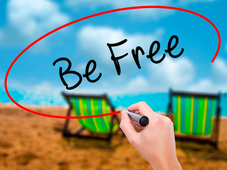 Man Hand writing Be Free with black marker on visual screen. Isolated on sunbed on the beach. Business, technology, internet concept. Stock Photo