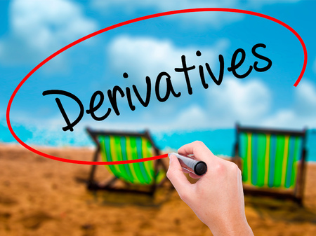 Man Hand writing Derivatives with black marker on visual screen. Isolated on sunbed on the beach. Business, technology, internet concept. Stock Photo