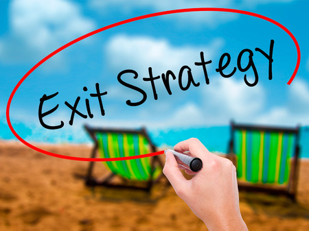 downsize: Man Hand writing Exit Strategy with black marker on visual screen. Isolated on sunbed on the beach. Business, technology, internet concept. Stock Photo