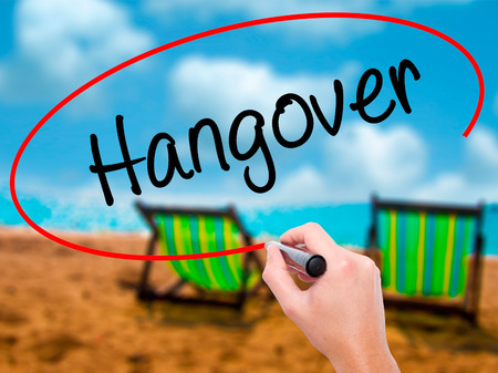 Man Hand writing Hangover with black marker on visual screen. Isolated on sunbed on the beach. Business, technology, internet concept. Stock Photo