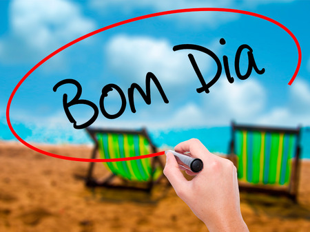 """Man Hand writing """"Bom Dia"""" (In portuguese - Good Morning)  with black marker on visual screen. Isolated on sunbed on the beach. Business, technology, internet concept. Stock Photo"""