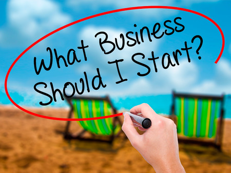 Man Hand writing What Business Should I Start? with black marker on visual screen. Isolated on sunbed on the beach. Business, technology, internet concept. Stock Photo