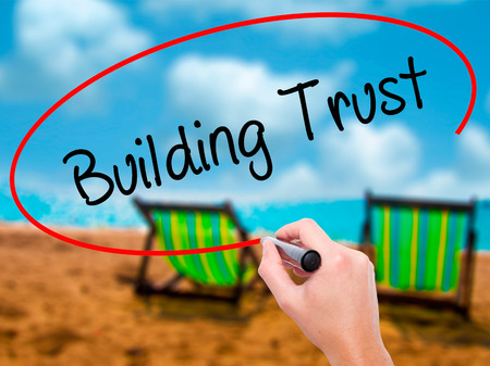 building trust: Man Hand writing Building Trust with black marker on visual screen. Isolated on sunbed on the beach. Business, technology, internet concept. Stock Photo Stock Photo