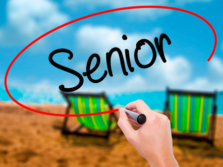 Man Hand writing Senior with black marker on visual screen. Isolated on sunbed on the beach. Business, technology, internet concept. Stock Photo