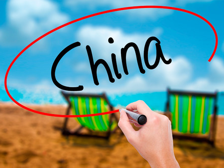Man Hand writing China with black marker on visual screen. Isolated on sunbed on the beach. Business, technology, internet concept. Stock Photo Stock Photo