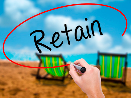 retained: Man Hand writing Retain with black marker on visual screen. Isolated on sunbed on the beach. Business, technology, internet concept. Stock Photo Foto de archivo