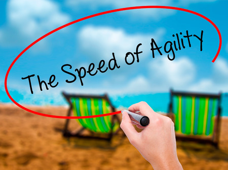 Man Hand writing The Speed of Agility with black marker on visual screen. Isolated on sunbed on the beach. Business, technology, internet concept. Stock Photo