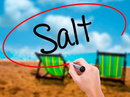 Man Hand writing Salt with black marker on visual screen. Isolated on sunbed on the beach. Business, technology, internet concept. Stock Photo