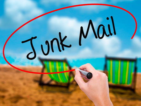 solicitors: Man Hand writing Junk Mail with black marker on visual screen. Isolated on sunbed on the beach. Business, technology, internet concept. Stock Photo