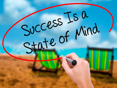aging brain: Man Hand writing Success Is a State of Mind with black marker on visual screen. Isolated on sunbed on the beach. Business, technology, internet concept. Stock Photo